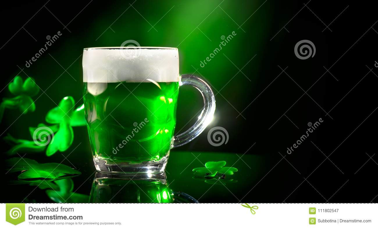 St. Patrick`s Day. Green beer pint over dark green background, decorated with shamrock leaves