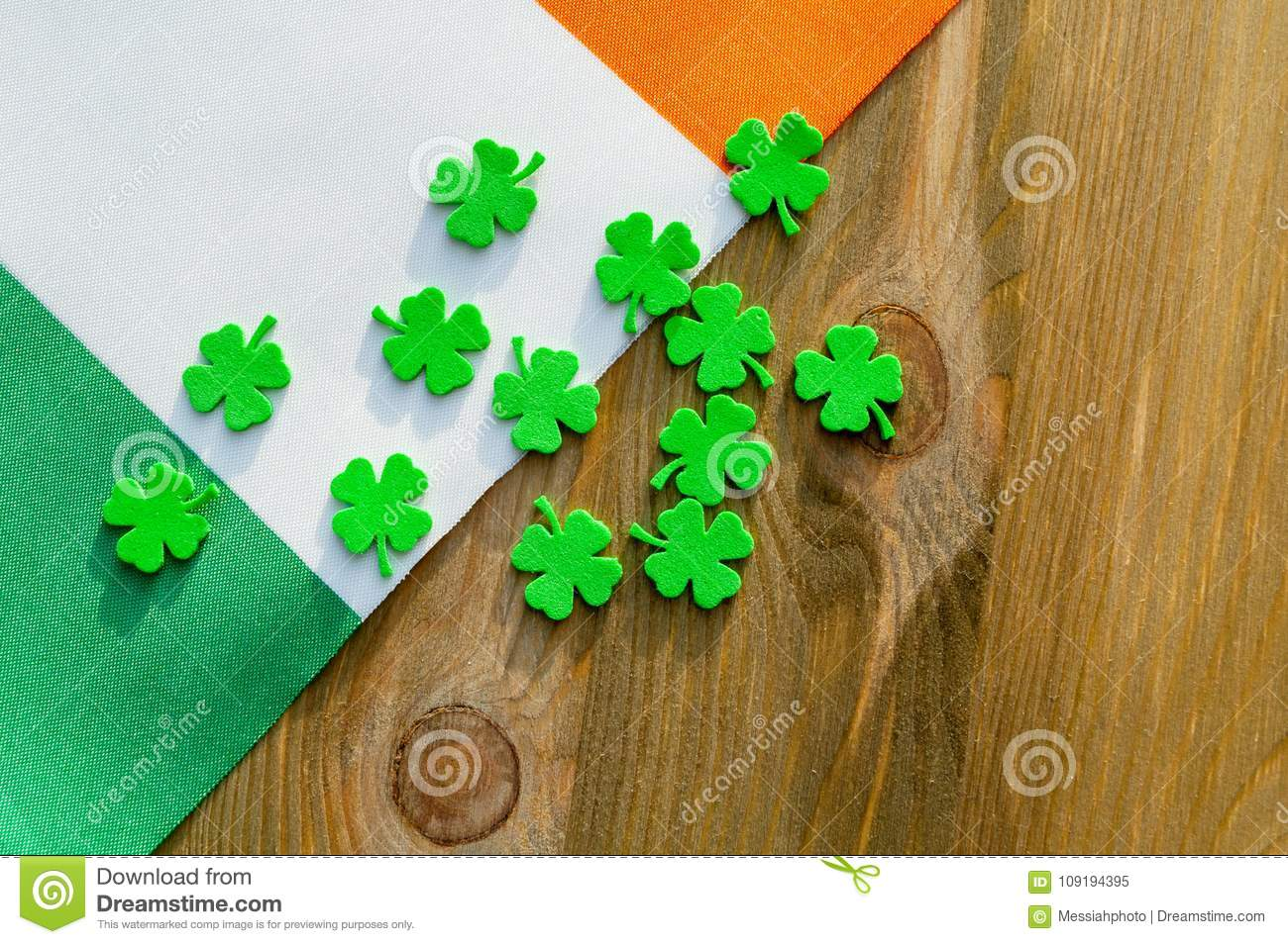 St Patrick`s Day holiday background. Green quatrefoils above the Irish national flag on the wooden background