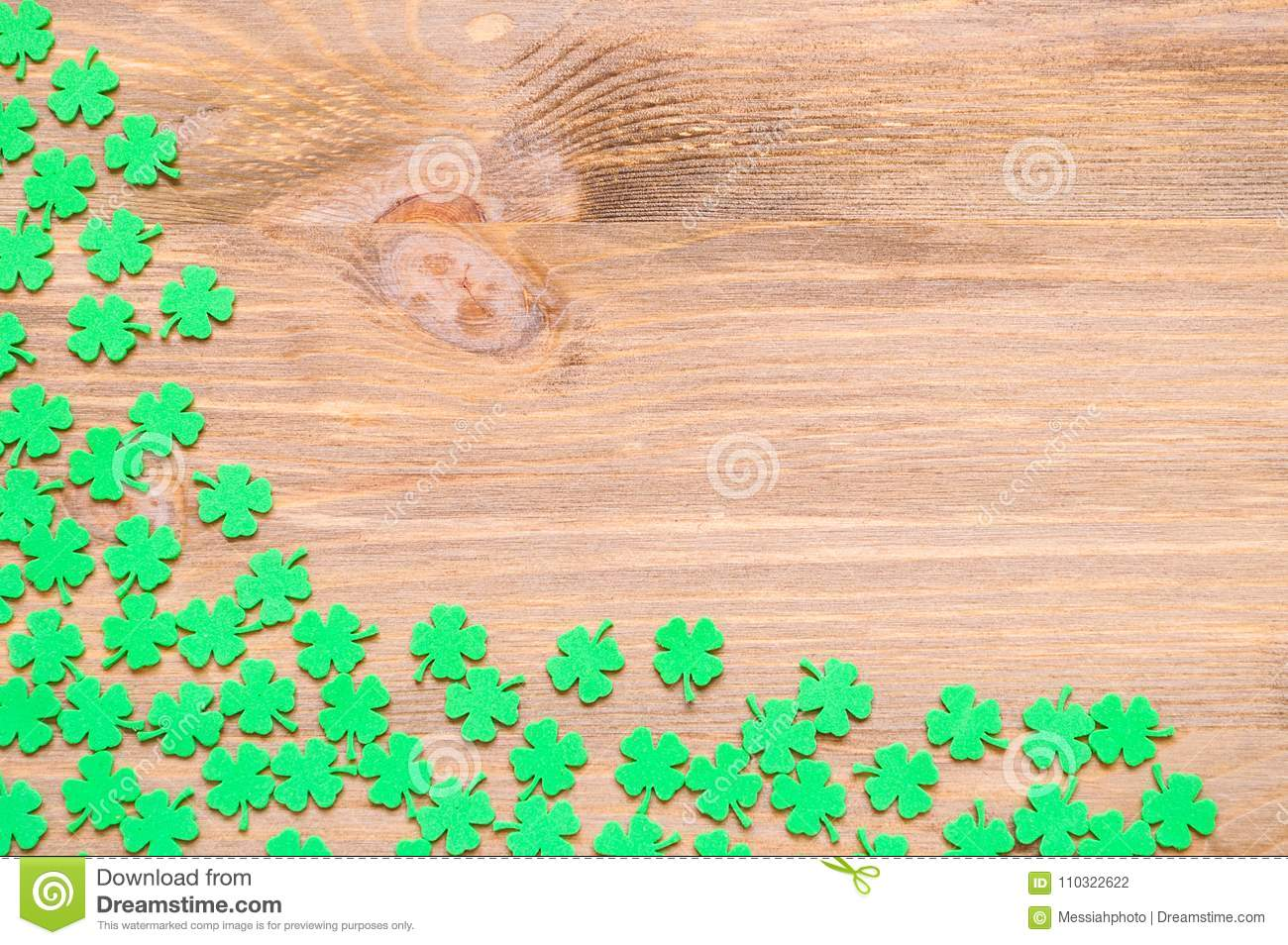 St Patricks Day background with green quatrefoils on wooden background, free space