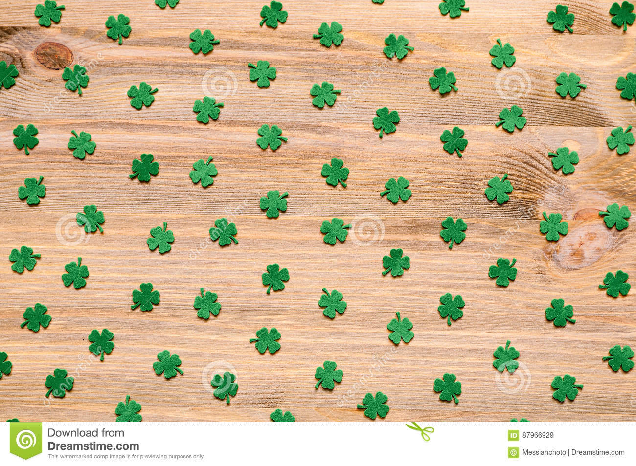 St Patricks Day background with green quatrefoils on the wooden background