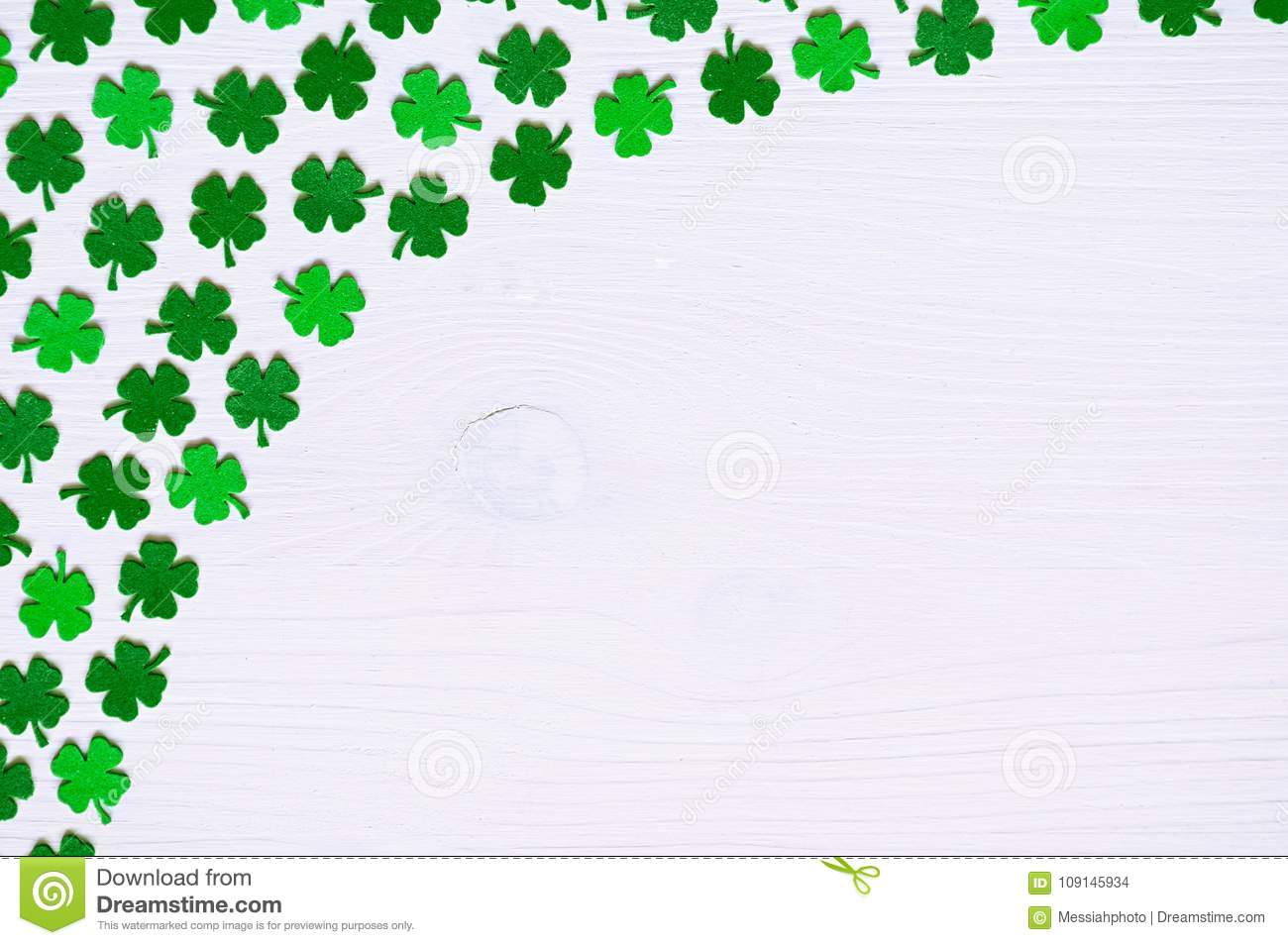 St Patricks Day background - one side curved border of green quatrefoils on the white wooden surface