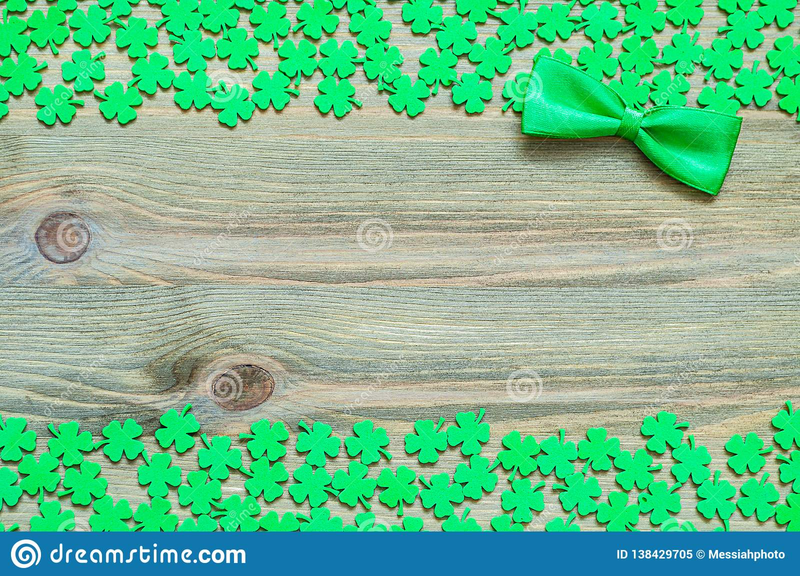 St Patricks Day festive background. Green quatrefoils and bow tie on the wooden background