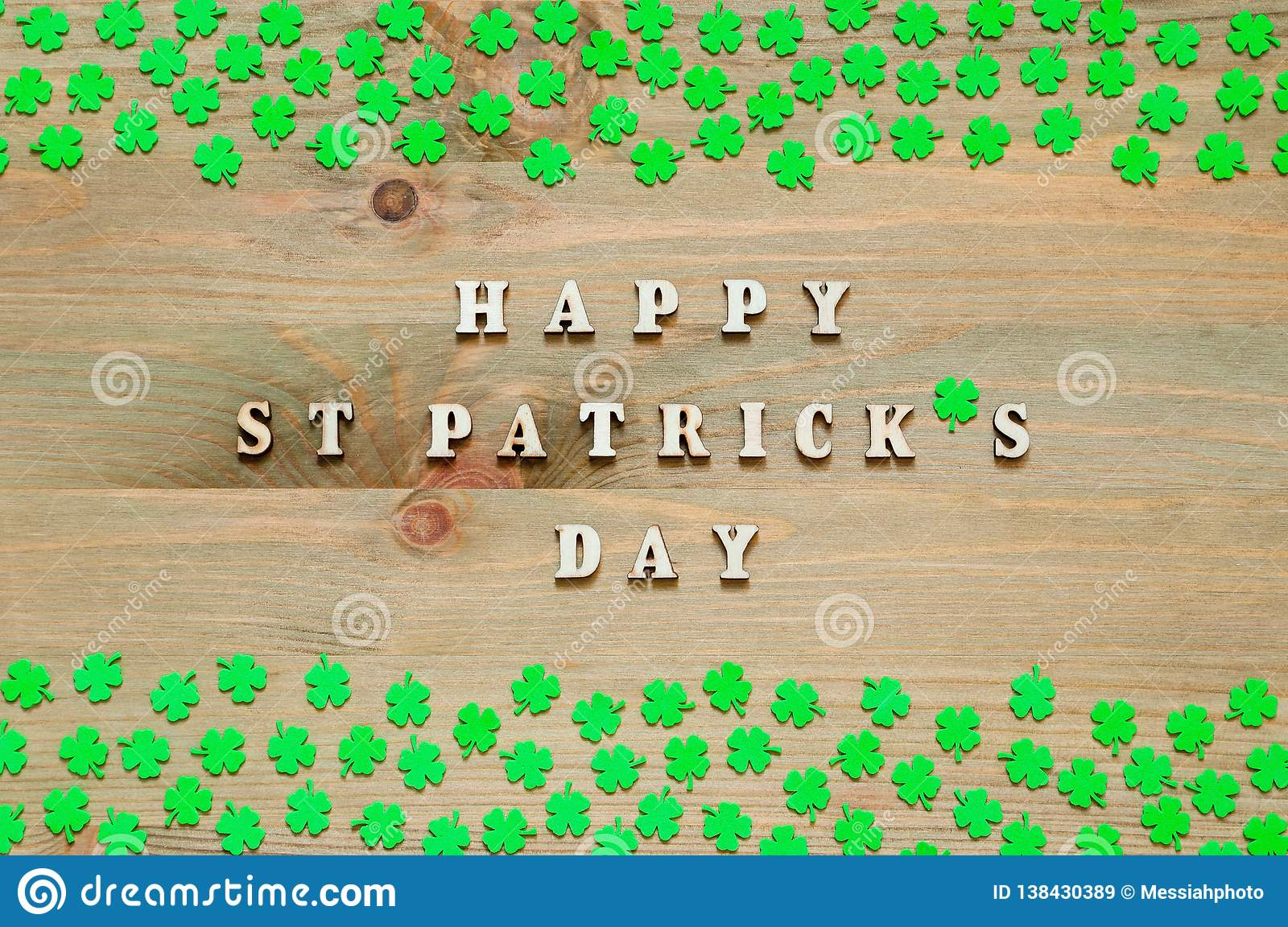 St Patricks Day festive background. Green quatrefoils on the wooden background and inscription Happy St Patrick`s day