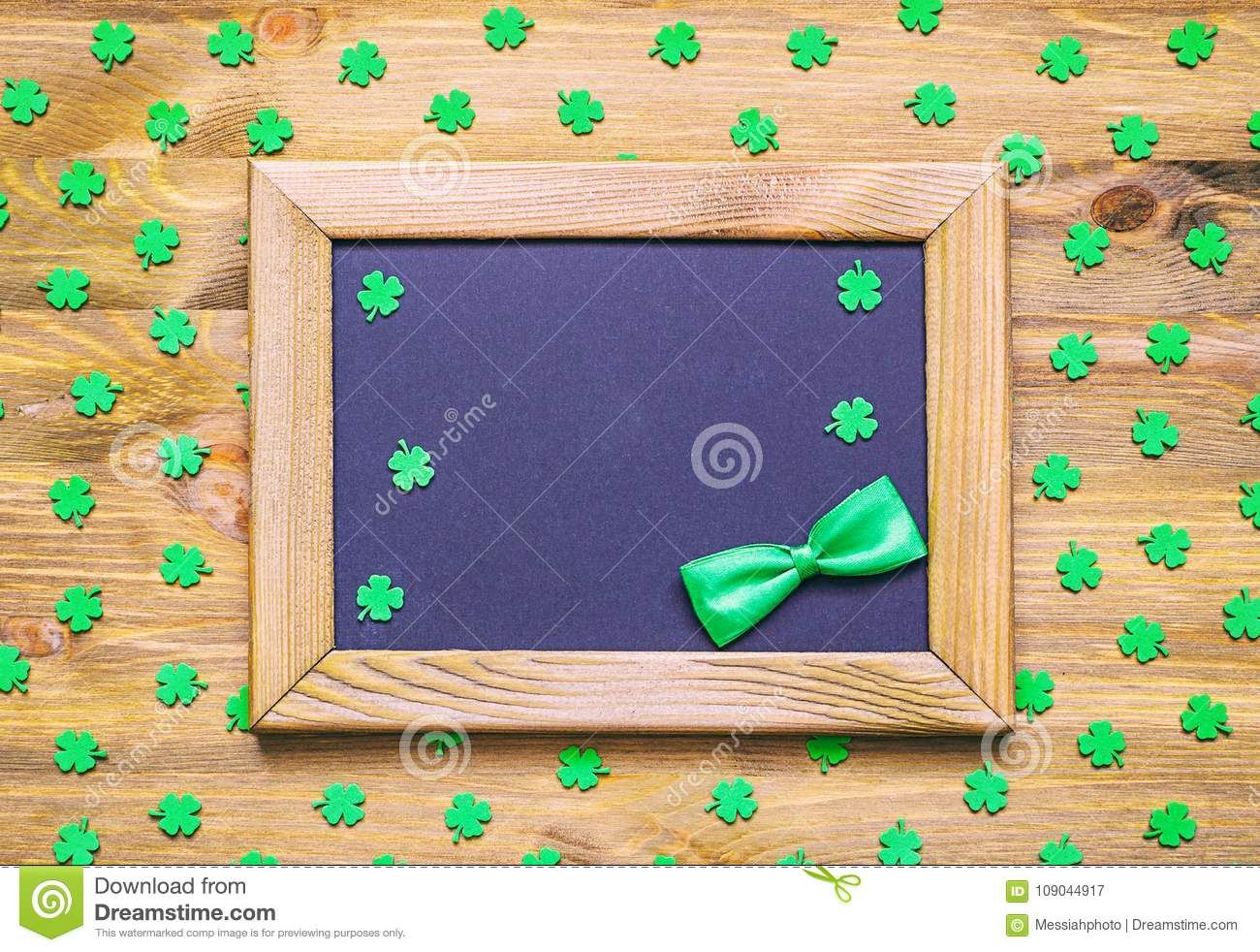 St Patricks Day holiday background with green quatrefoils and frame with green bow tie on the wooden background