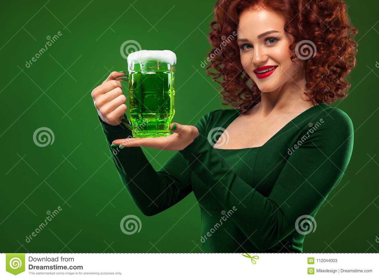 St Patricks Day. Young and redhead Octoberfest waitress, wearing a dress, serving big beer mugs on green background