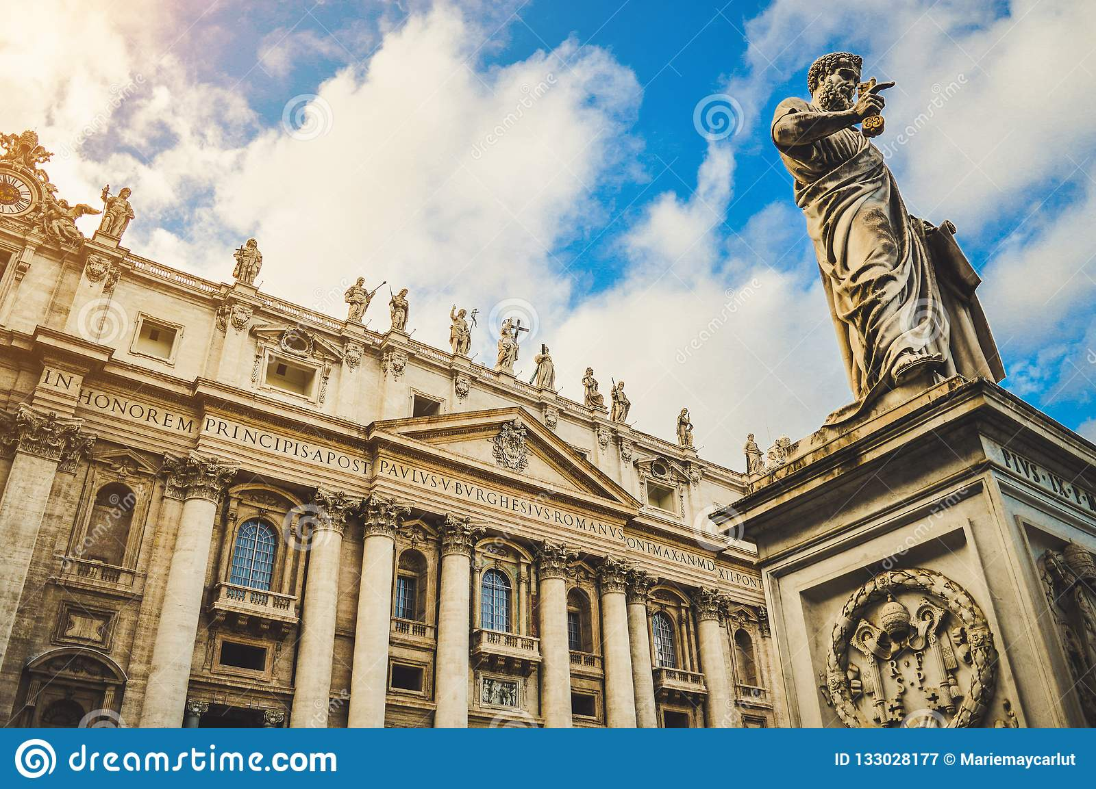 St. Peter`s square, Vatican City, Roma. Low angle view of the statue of St. Peter with the front of the Basilica in the background