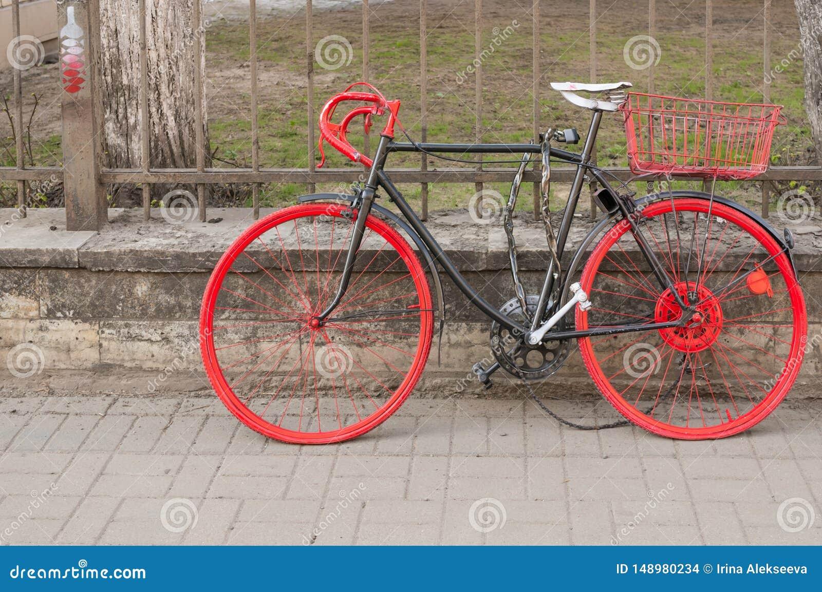 St Petersburg, R?ssia - 04 26 2019: Bicicleta velha colorida perto da cerca no passeio na cidade