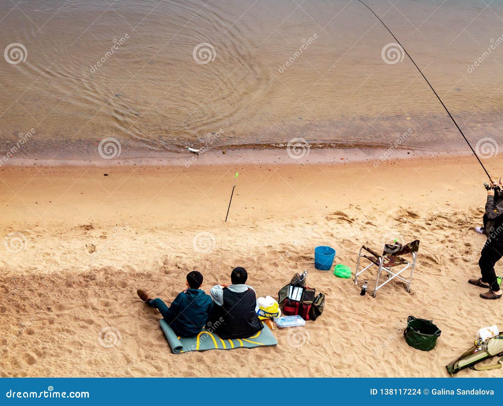 St. Petersburg, Rusland - Juli 10, 2018: De groep vissers vist op de zandige kusten van de Golf van Finland onder de brug