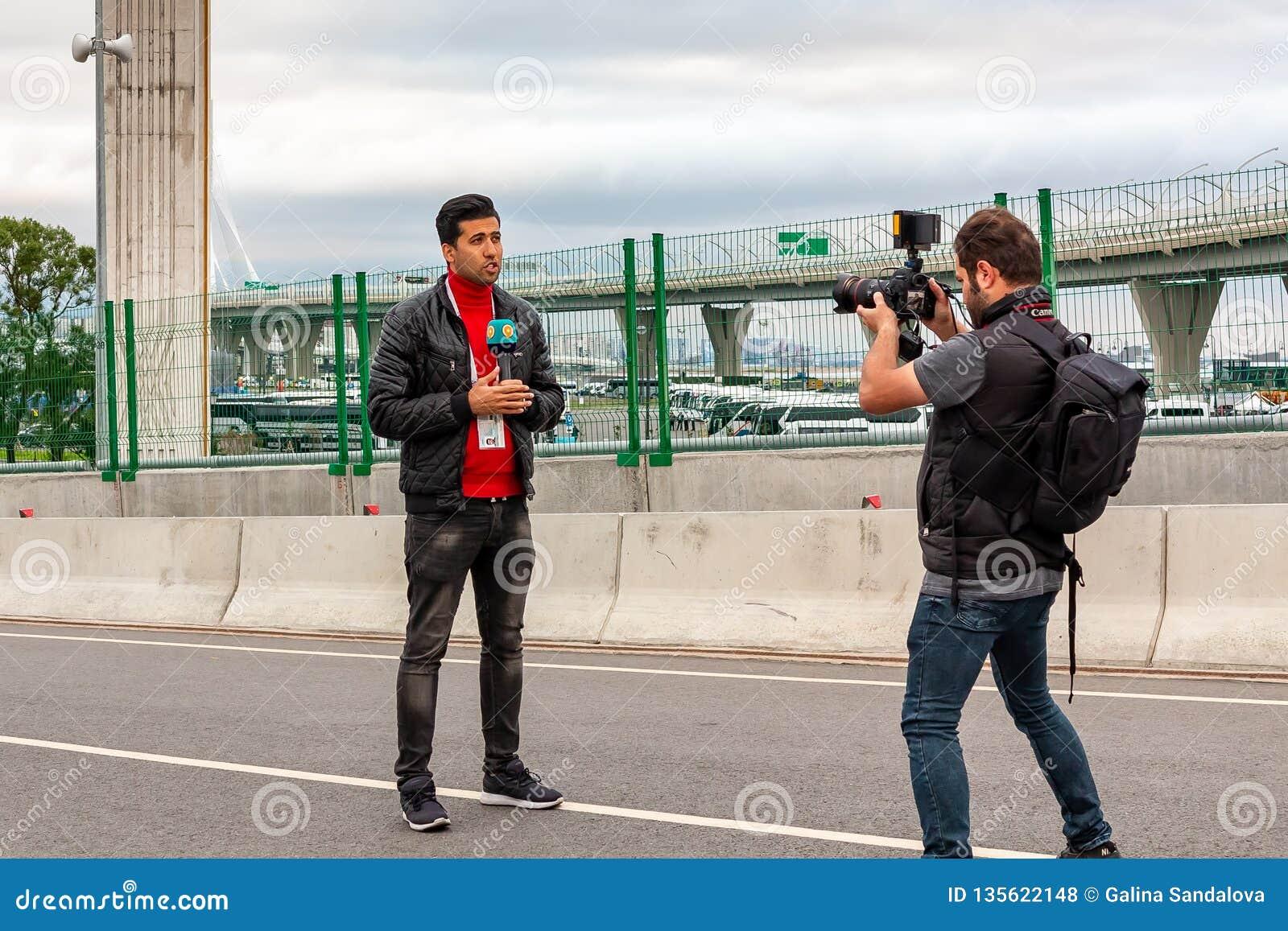 St. Petersburg, Rusland - Juli 10, 2018: TV-de Verslaggevers melden levend van de Jachtbrug vóór de voetbalwedstrijd in St