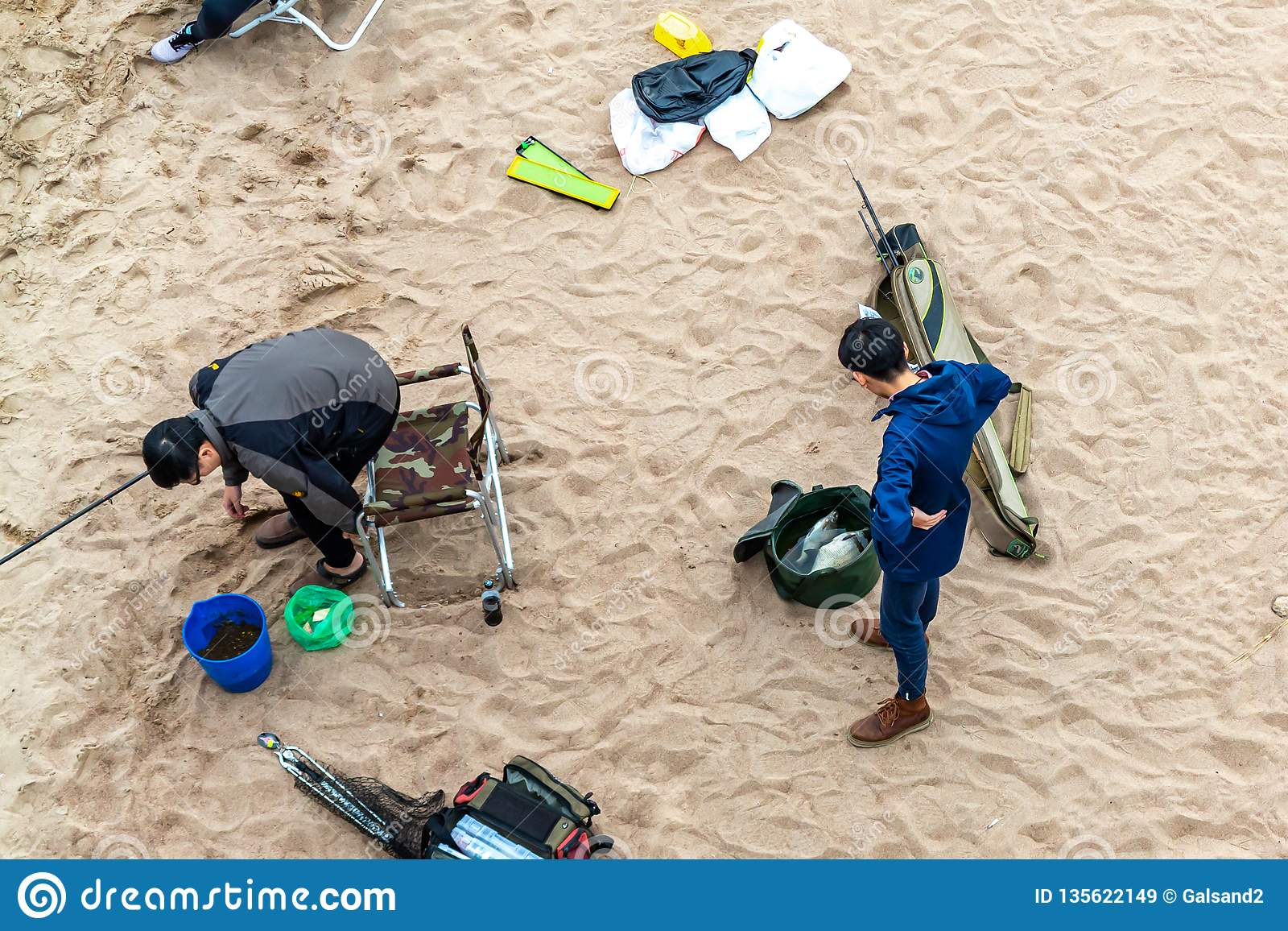 St. Petersburg, Russia - July 10, 2018: Group of fishermen are fishing on the sandy shores of the Gulf of Finland under the bridge
