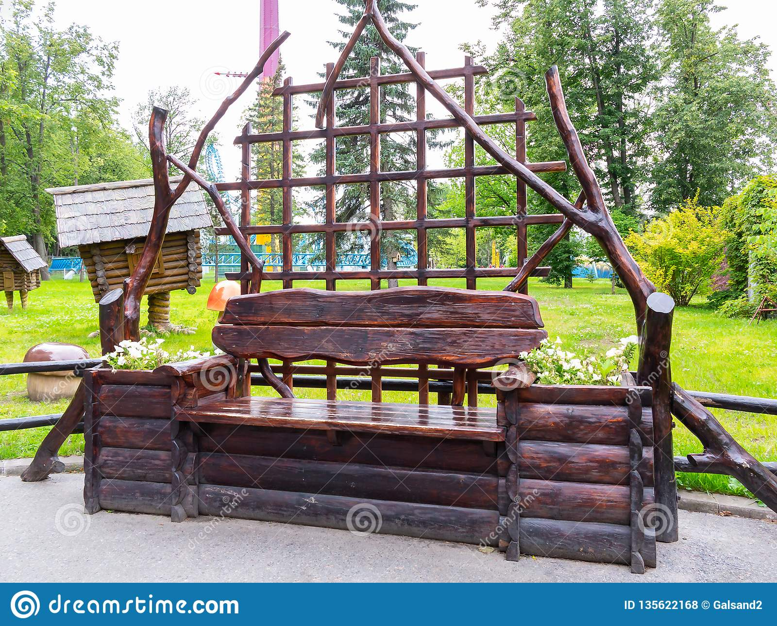 St. Petersburg, Russia - July 10, 2018: Wooden bench made of logs with a back in the city park