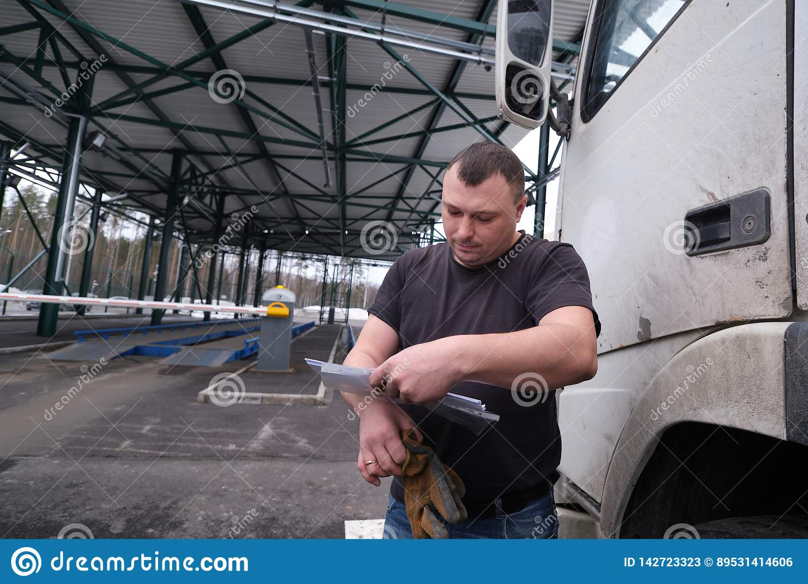 Truck Driver With A Package Of Declarations At Customs