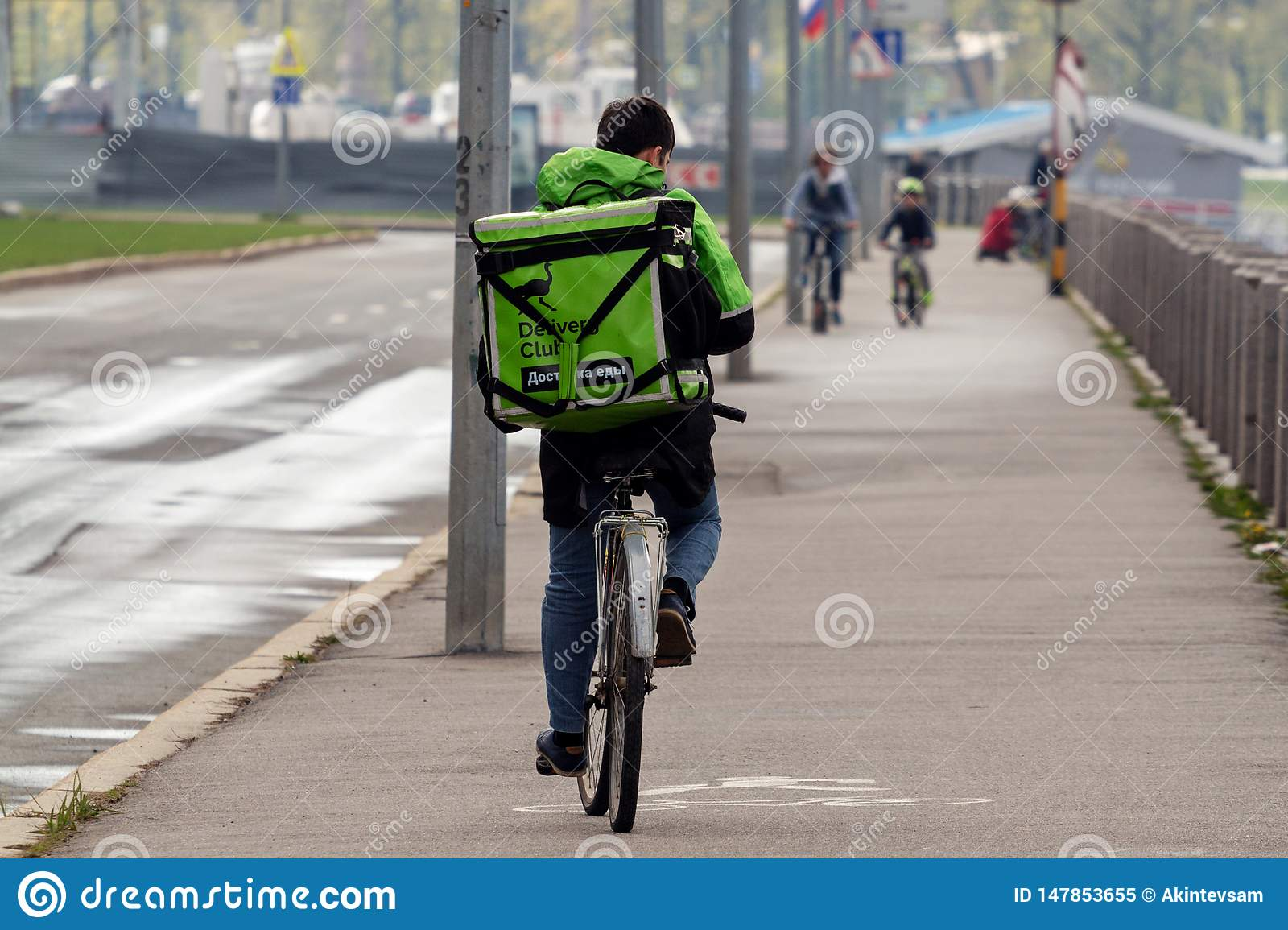 Courier of Delivery club delivers food on a bicycle