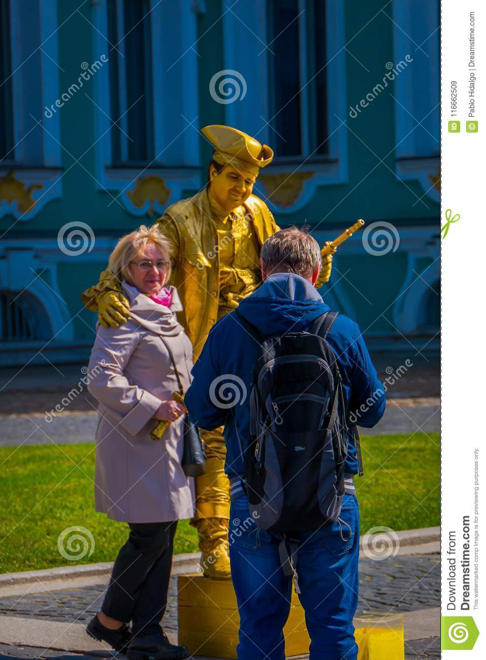 ST. PETERSBURG, RUSSIA, 01 MAY 2018: Unidentified couple close to golden paint mime artist or living golden statue