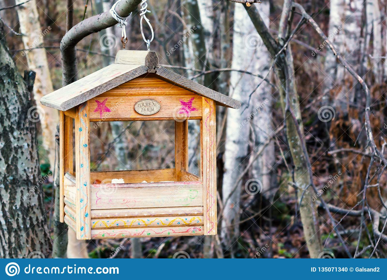 St. Petersburg, Russia - November 22, 2018:: Bird feeder in the shape of a house on a branch in the winter forest