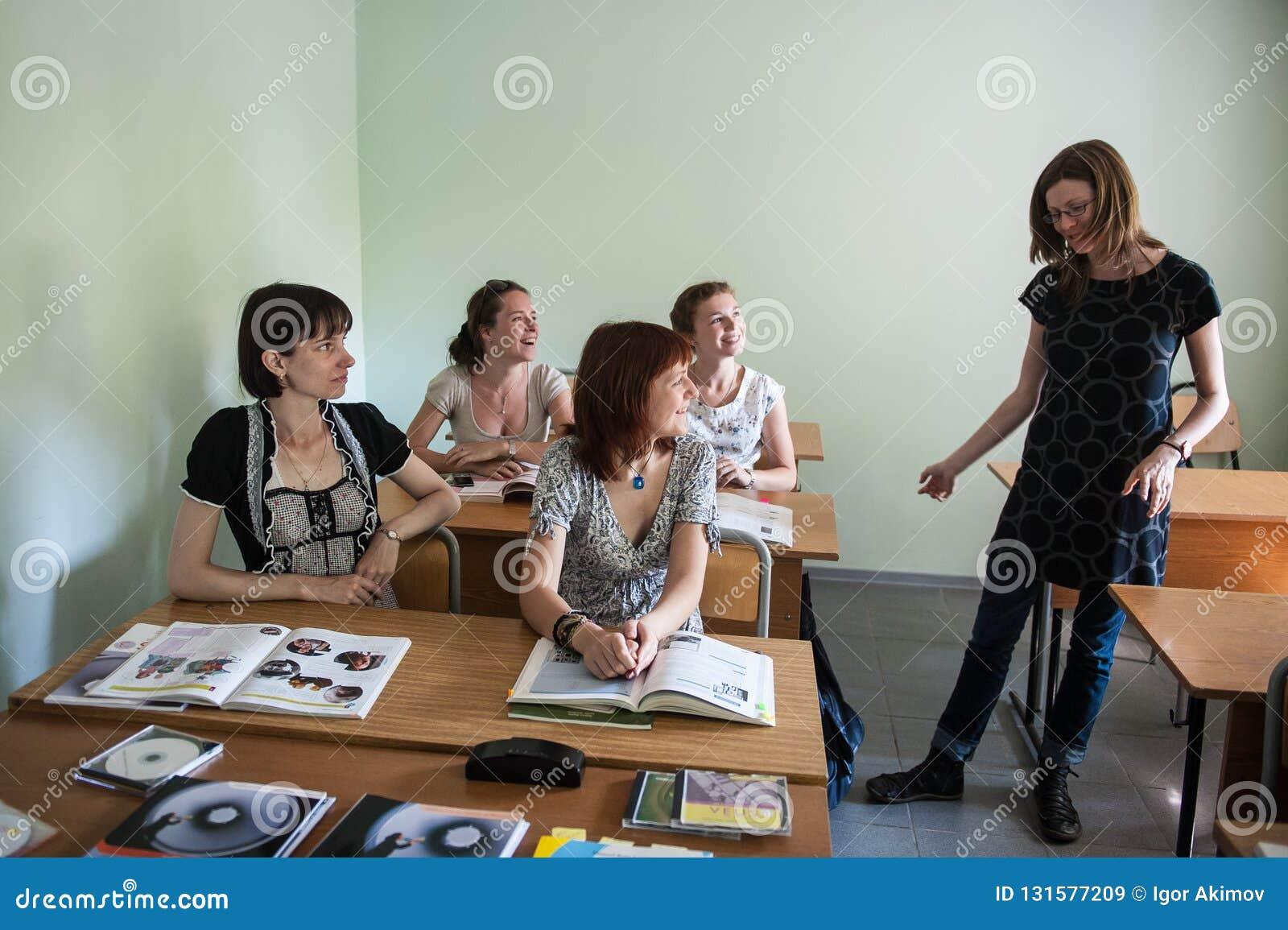 St Petersburg, Russland - 10. Juni 2018: Fremdsprachenlehrer der jungen Frau in einem kleinen Klassenzimmer gibt Studenten eine L