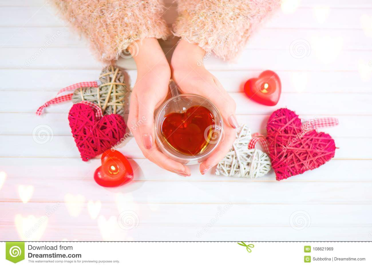 St. Valentine`s Day. Young woman hands holding heart shaped tea cup over wooden background