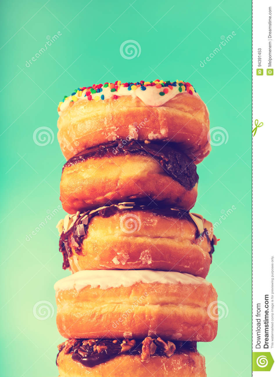 Stack of assorted donuts on blue green background