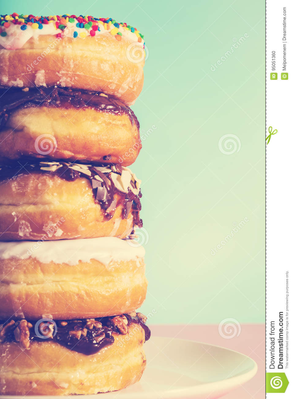 Stack of assorted donuts on pastel blue and pink background