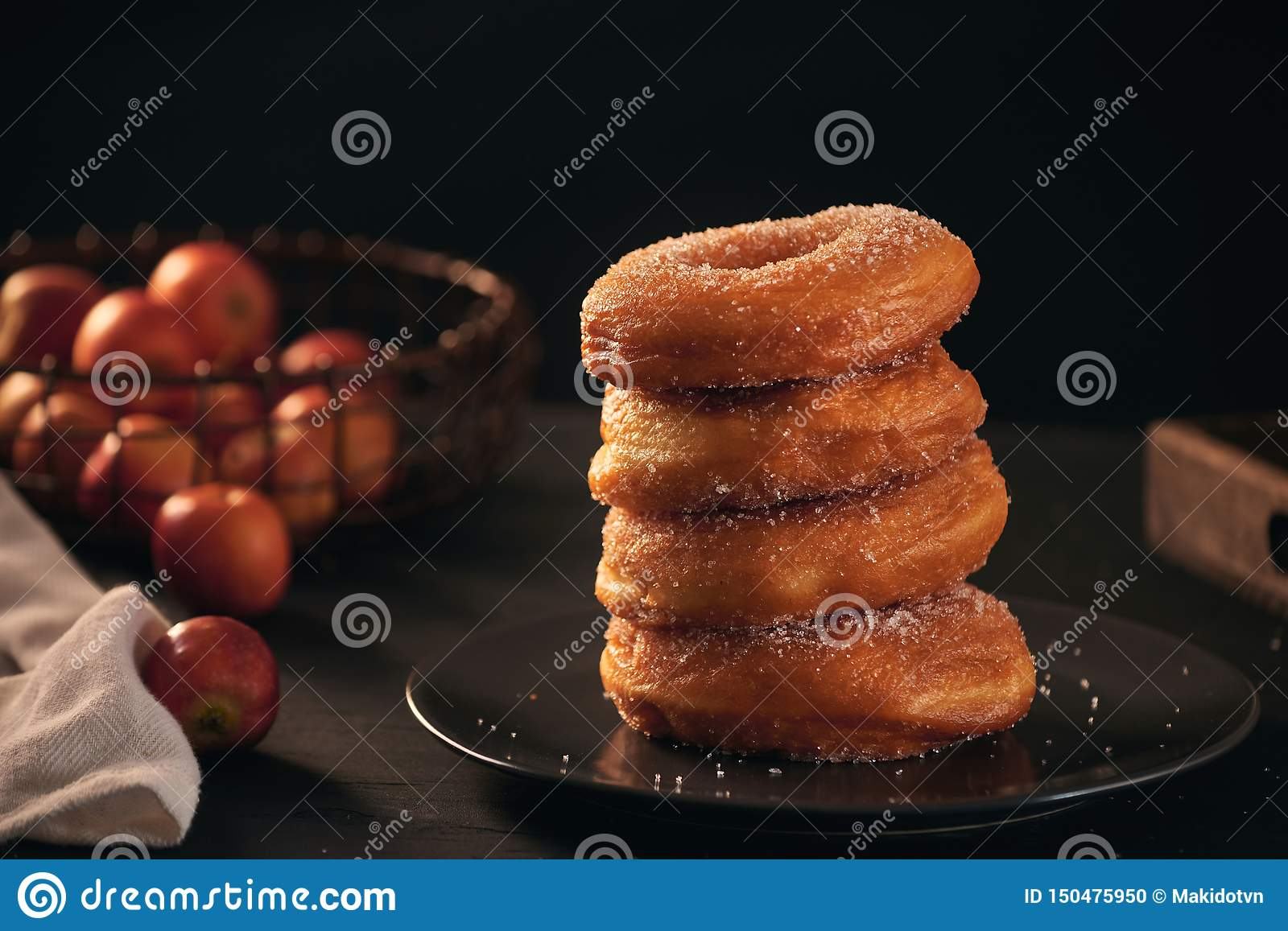Stack of assorted donuts on a plate with milk on black background