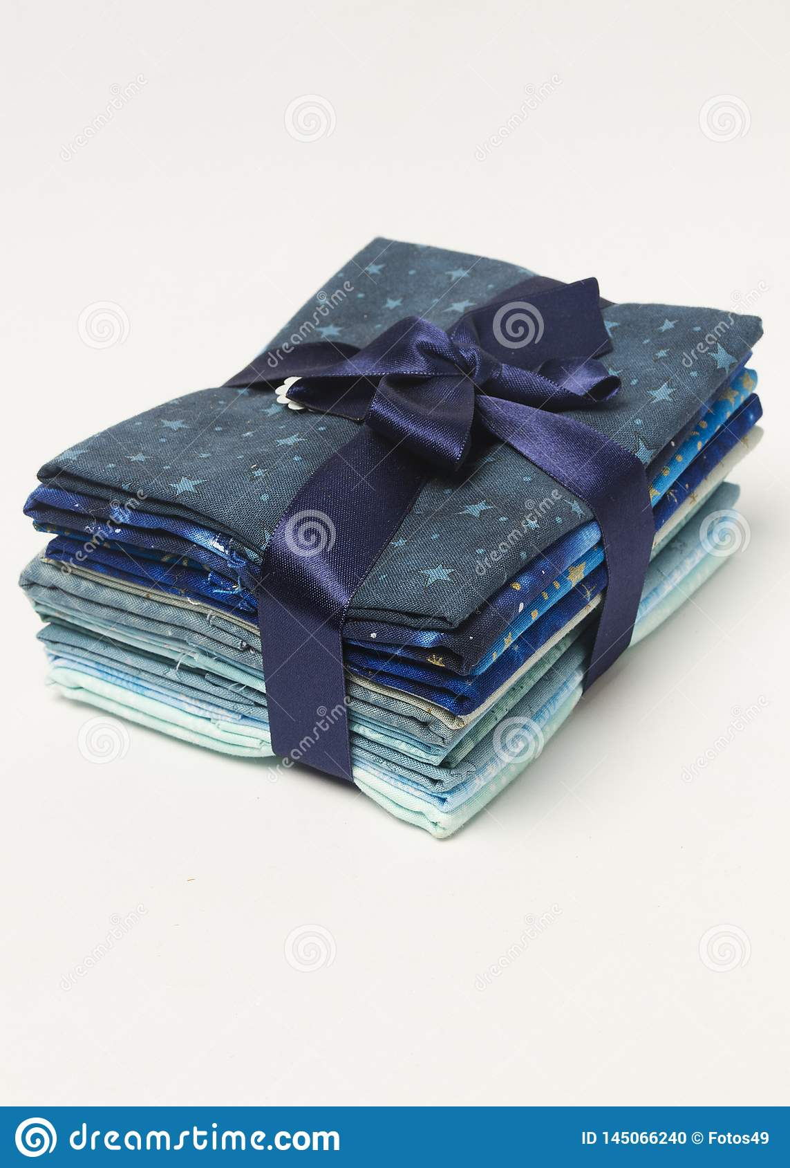 Stack of blue shades folded fabrics with gift ribbon from above