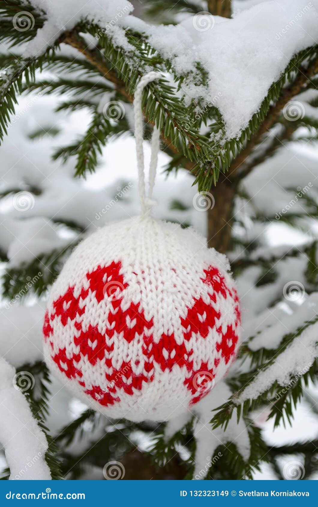 Stack bollar för garnering för nytt år som och julgranhänger på den prydliga filialen som täckas med snö