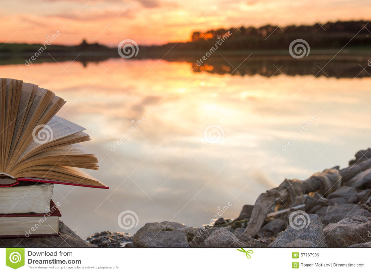 Stack of book and Open hardback book on blurred nature landscape backdrop against sunset sky with back light. Copy space, back to