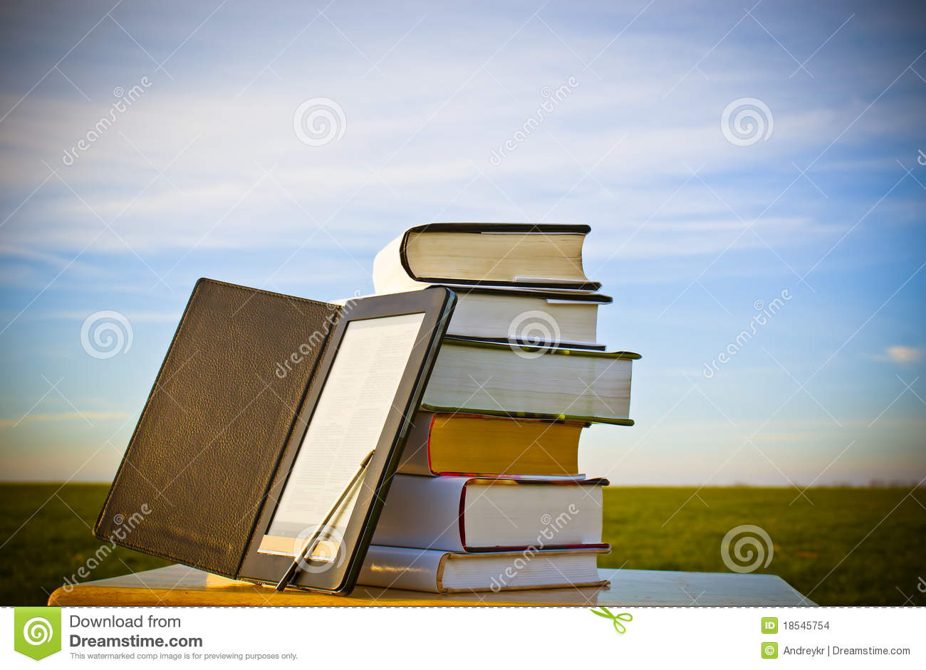 Stack of books with ebook reader