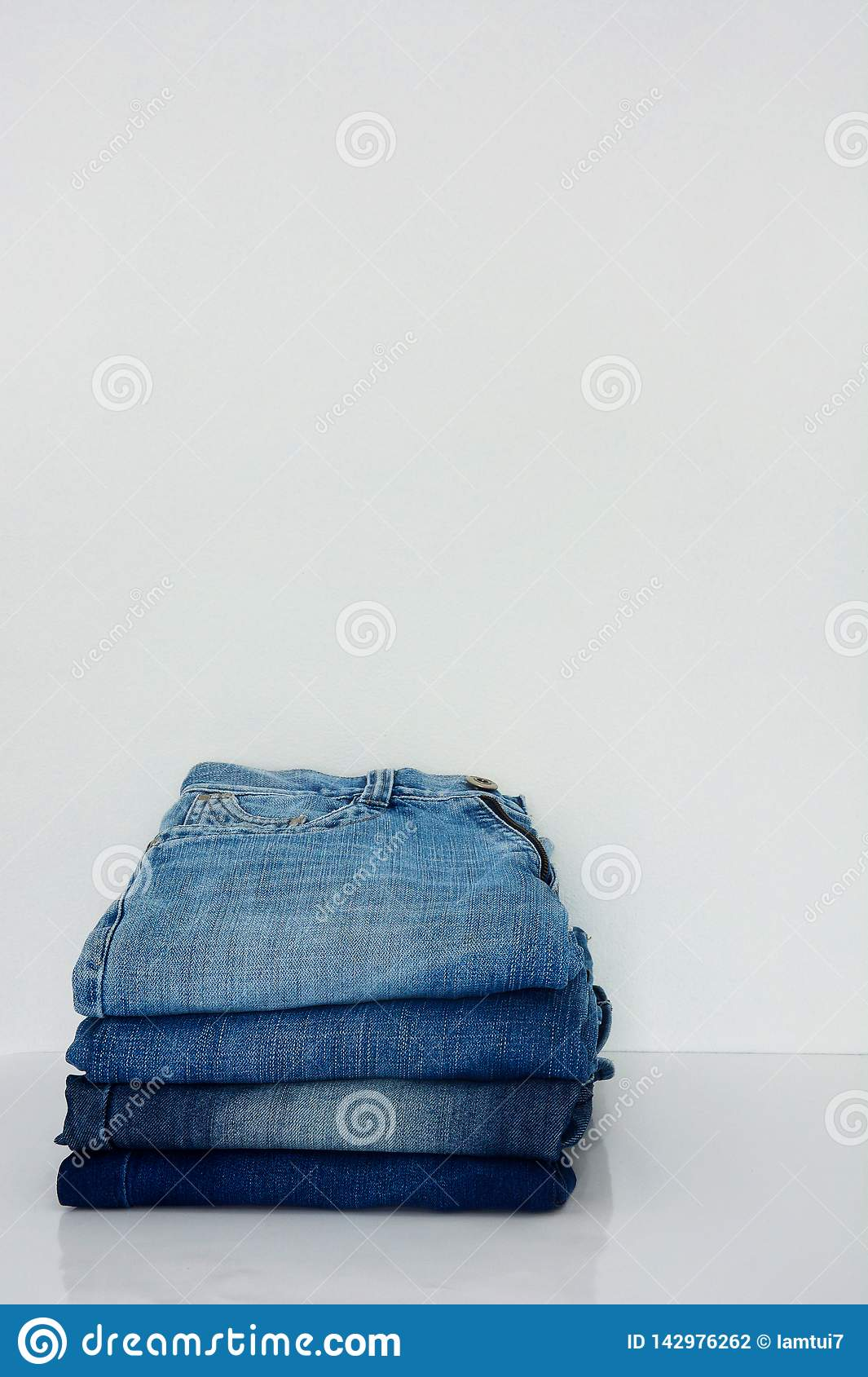 Stack of blue jeans on white background