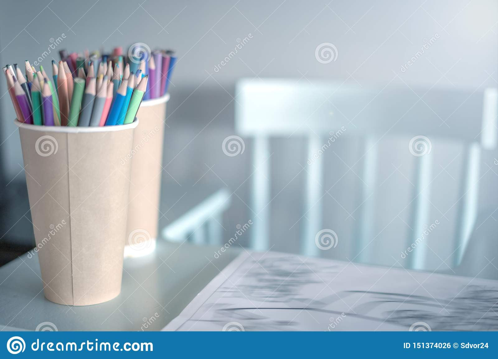 Stack of colored pencils in a glass on children`s table, next to a high chair ,left, A cozy place to draw for kids.