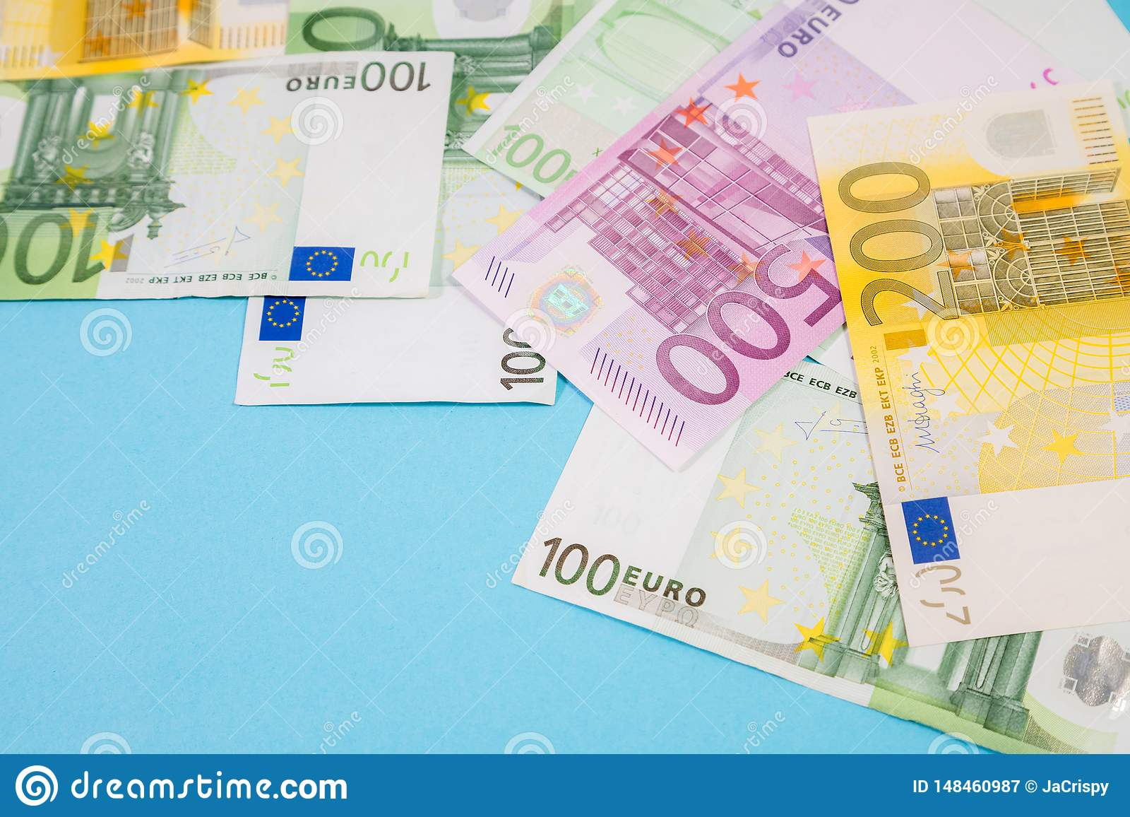 Stack of Euro bank notes on blue background in the studio with space for text