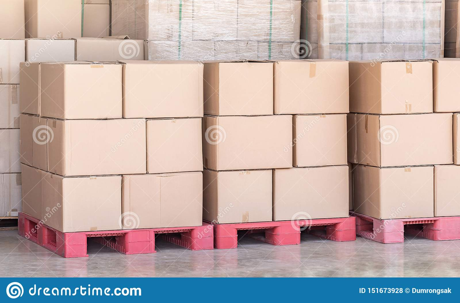 Stack of goods carton boxes on red pallet at logistics warehouse