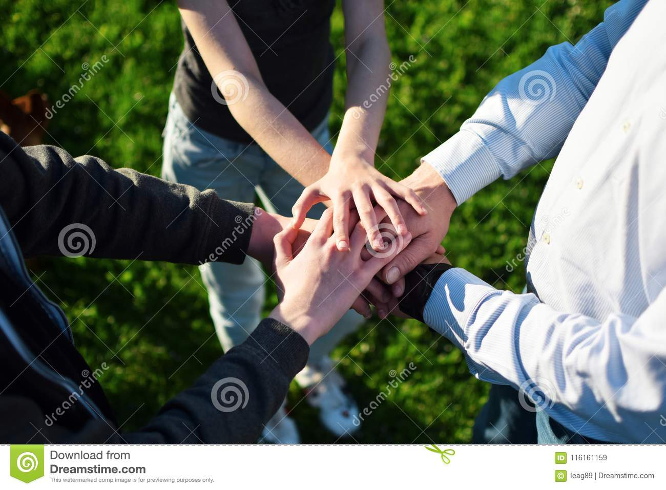 Stack Of Hands On Green Grass Background Stock Image - Image