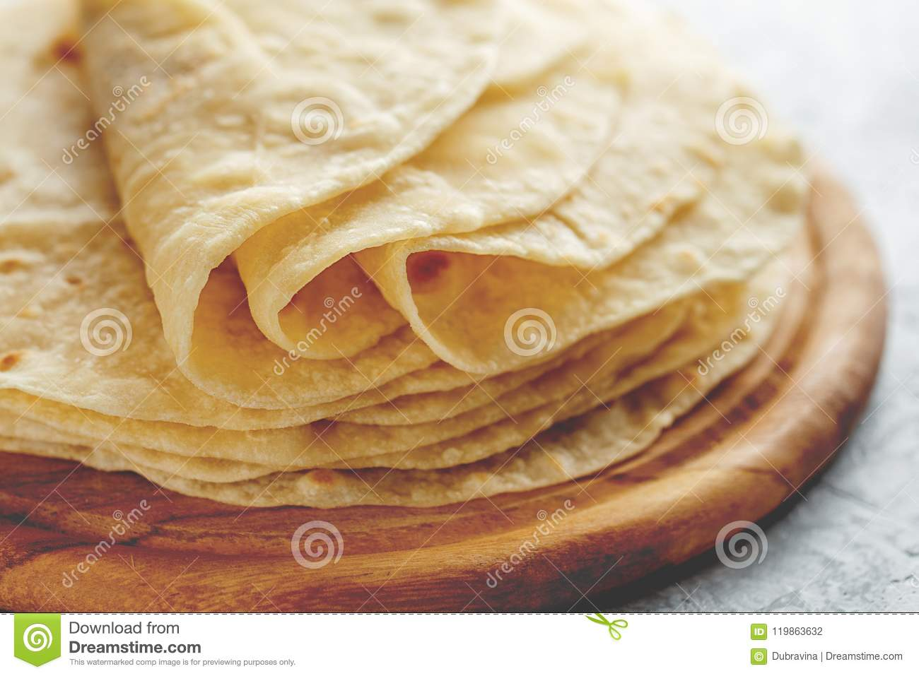 Stack of homemade wheat flour tortilla wraps on wooden cutting board.