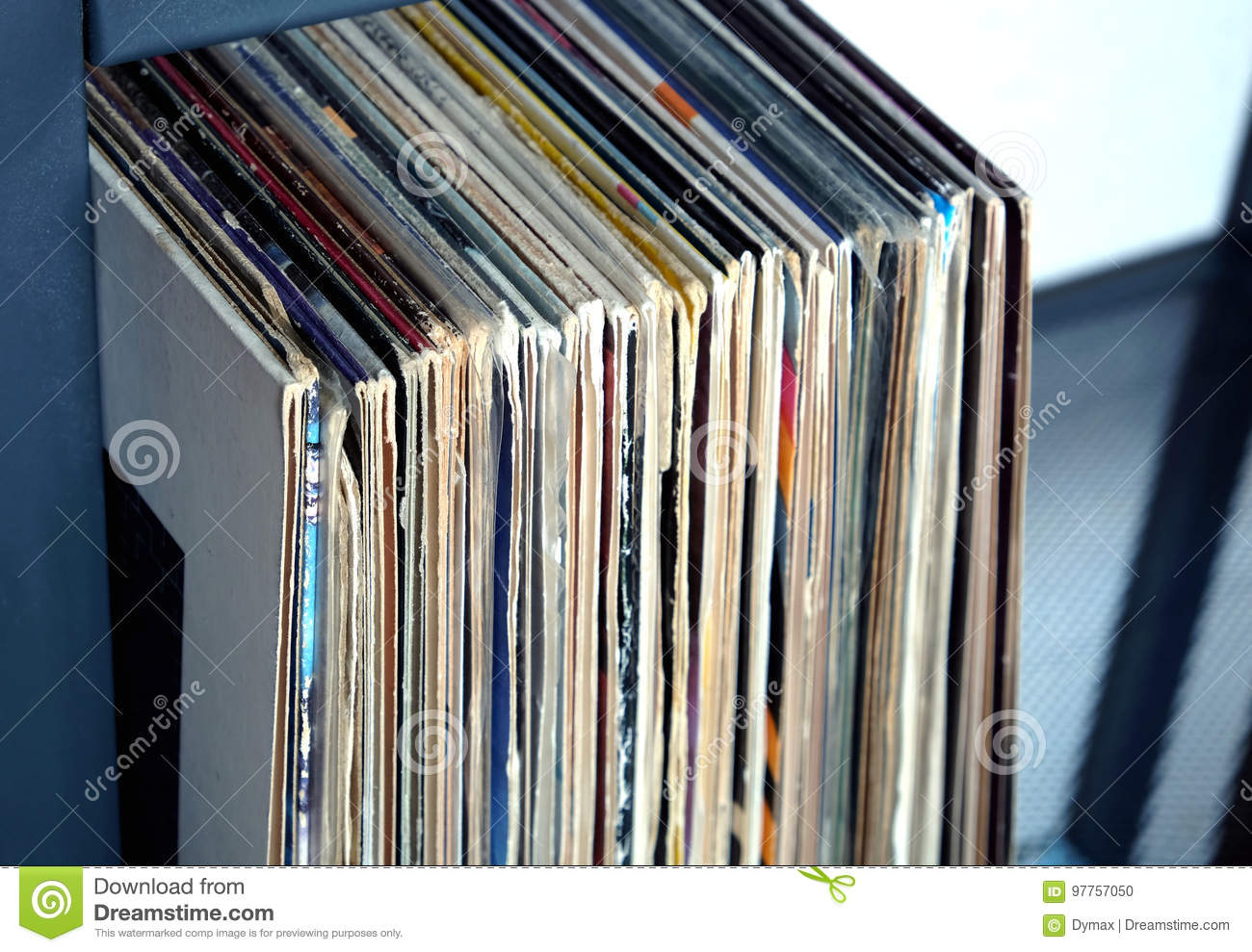 Stack of many vinyl records in old color covers on a shelf side view