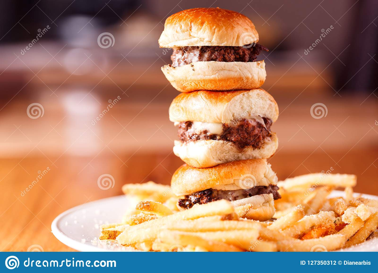 Stack of mini cheeseburgers with fries