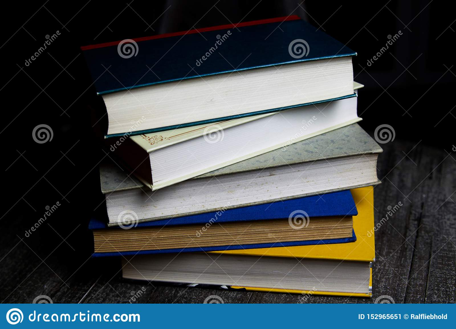 Stack of old books on round wood table with reading light during night