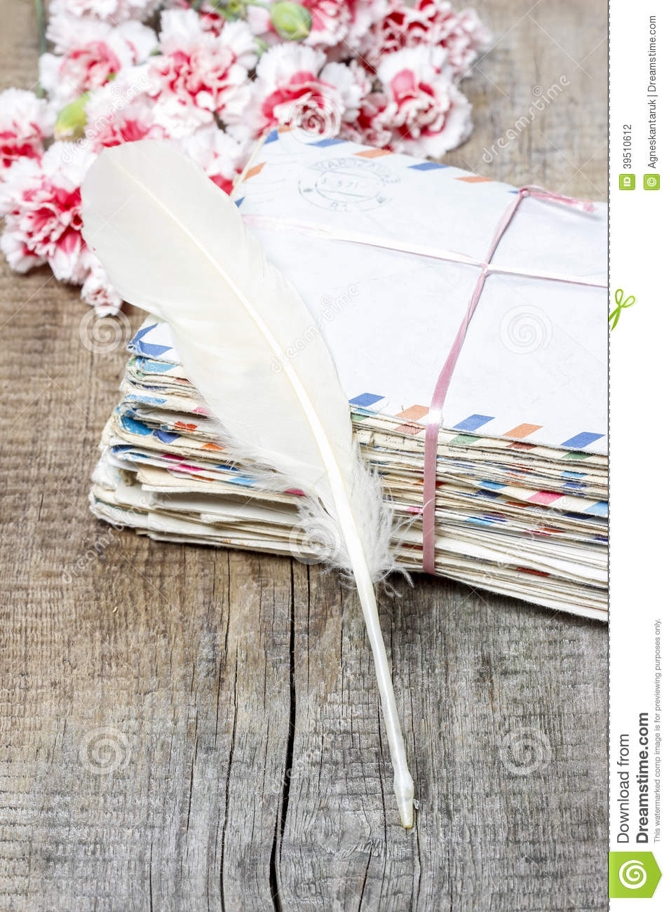 Stack of old letters, feather pen and bouquet