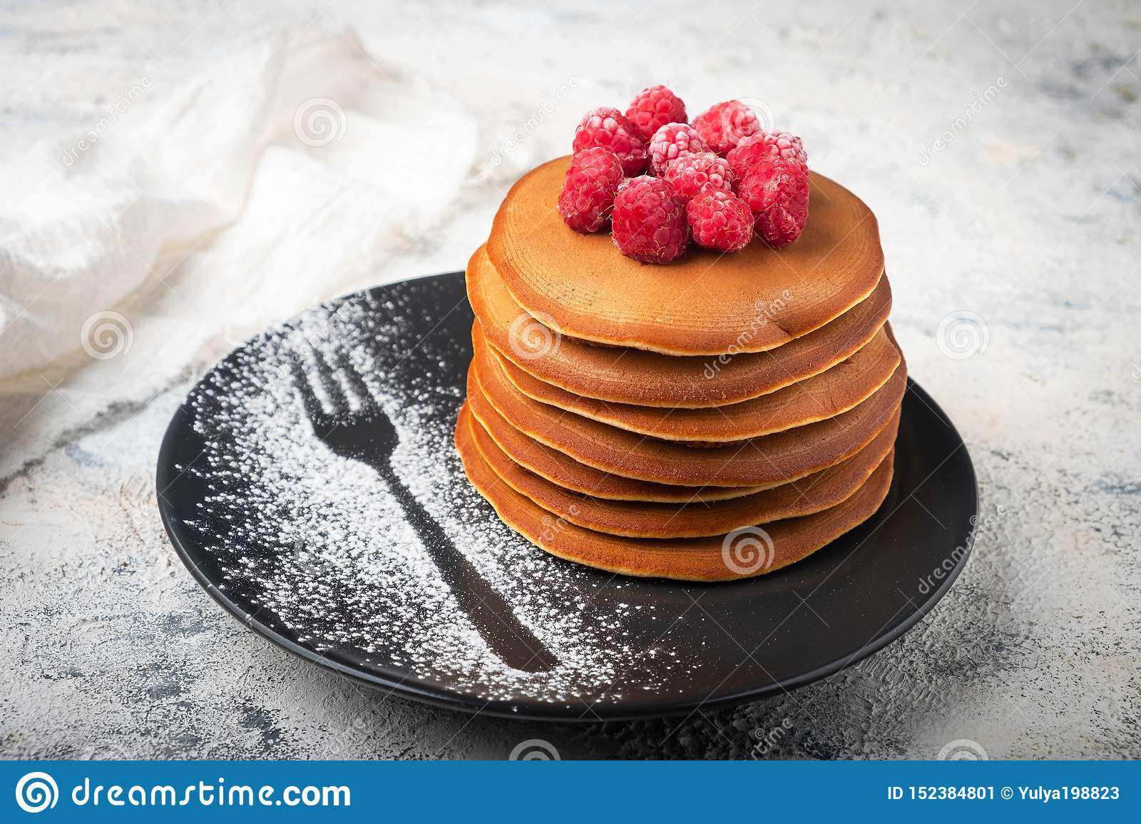 A stack of pancakes on a plate with raspberries and berry sauce