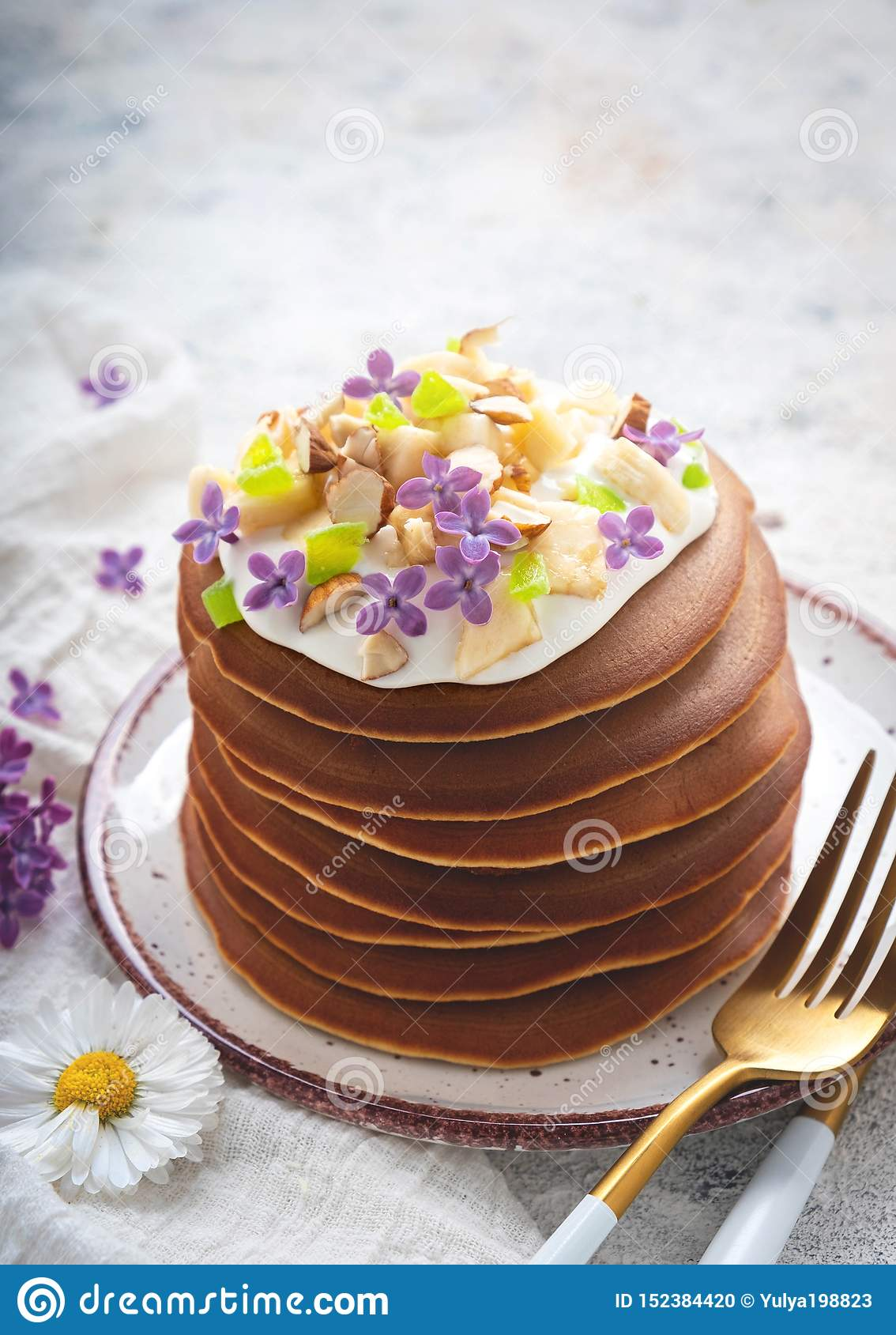 A stack of pancakes on a plate with sauce, bananas, candied fruits and decorated with flowers, Close-up,