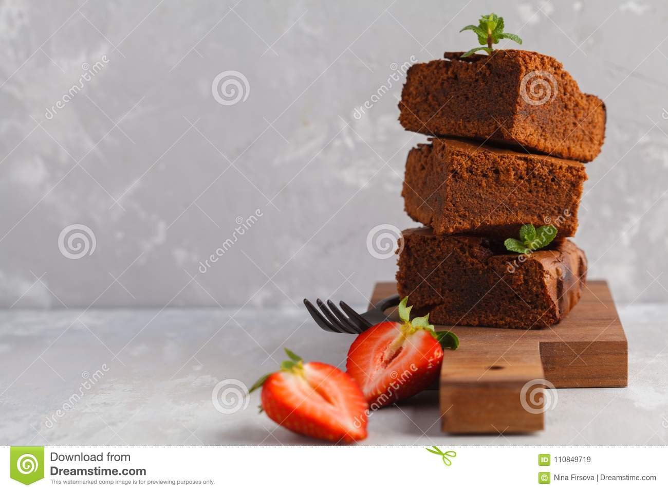 Stack Of Pieces Of Homemade Dark Chocolate Brownie With Strawberries