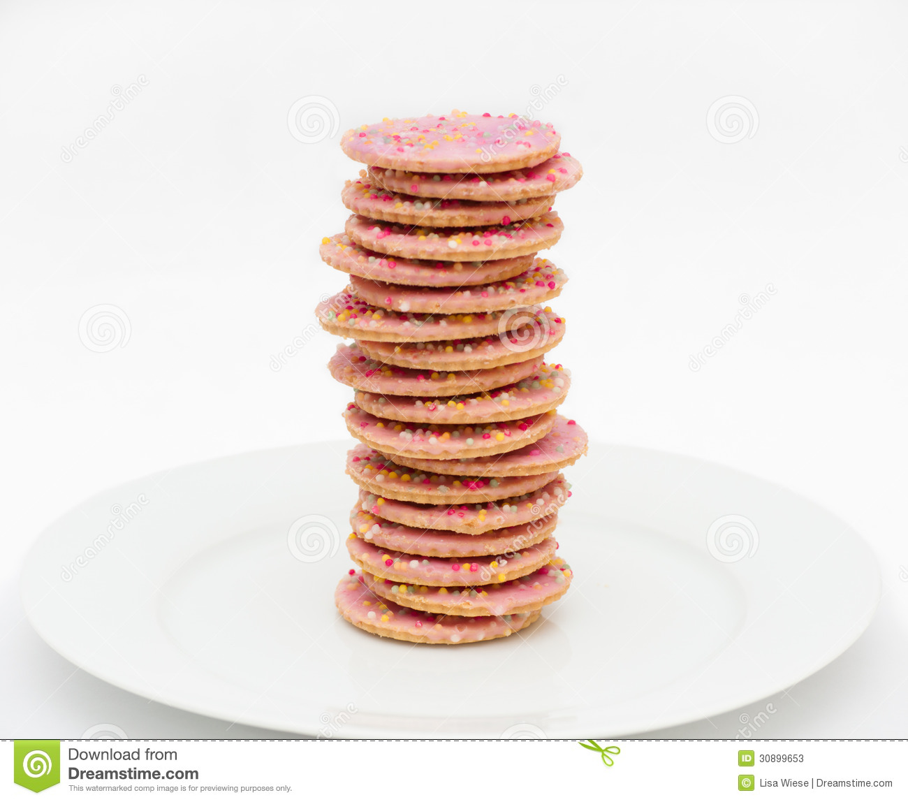 Pink icing cookies / biscuits with sprinkles, casually stacked on a ...