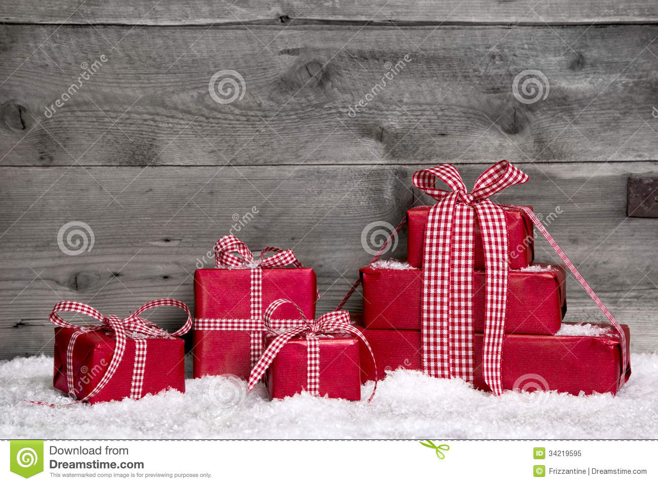 Stack of red christmas gifts snow on grey wooden