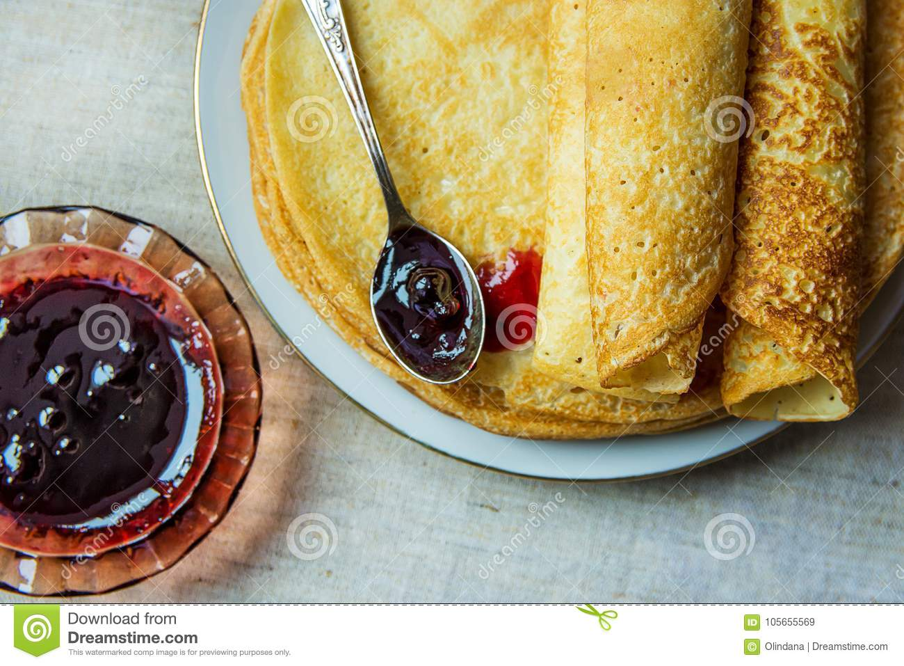 Stack of Rolled Golden Crepes on White Plate Black Currant Jam in Crystal Rosette Spoon Linen Tablecloth