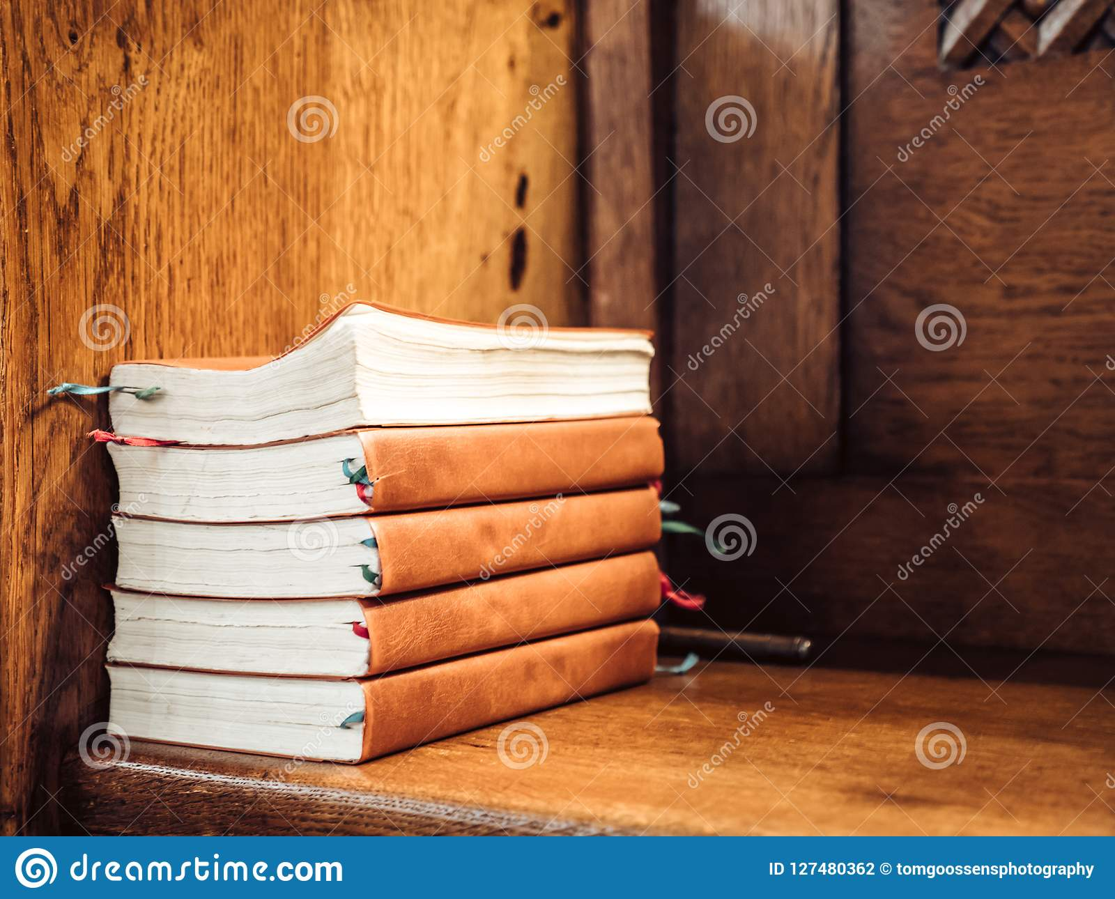 Stack of songbooks on a wooden bench in a church
