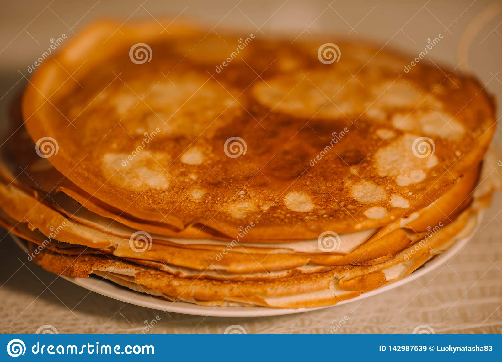 A stack of thin Russian hot pancakes blini  with steam emanating from them.