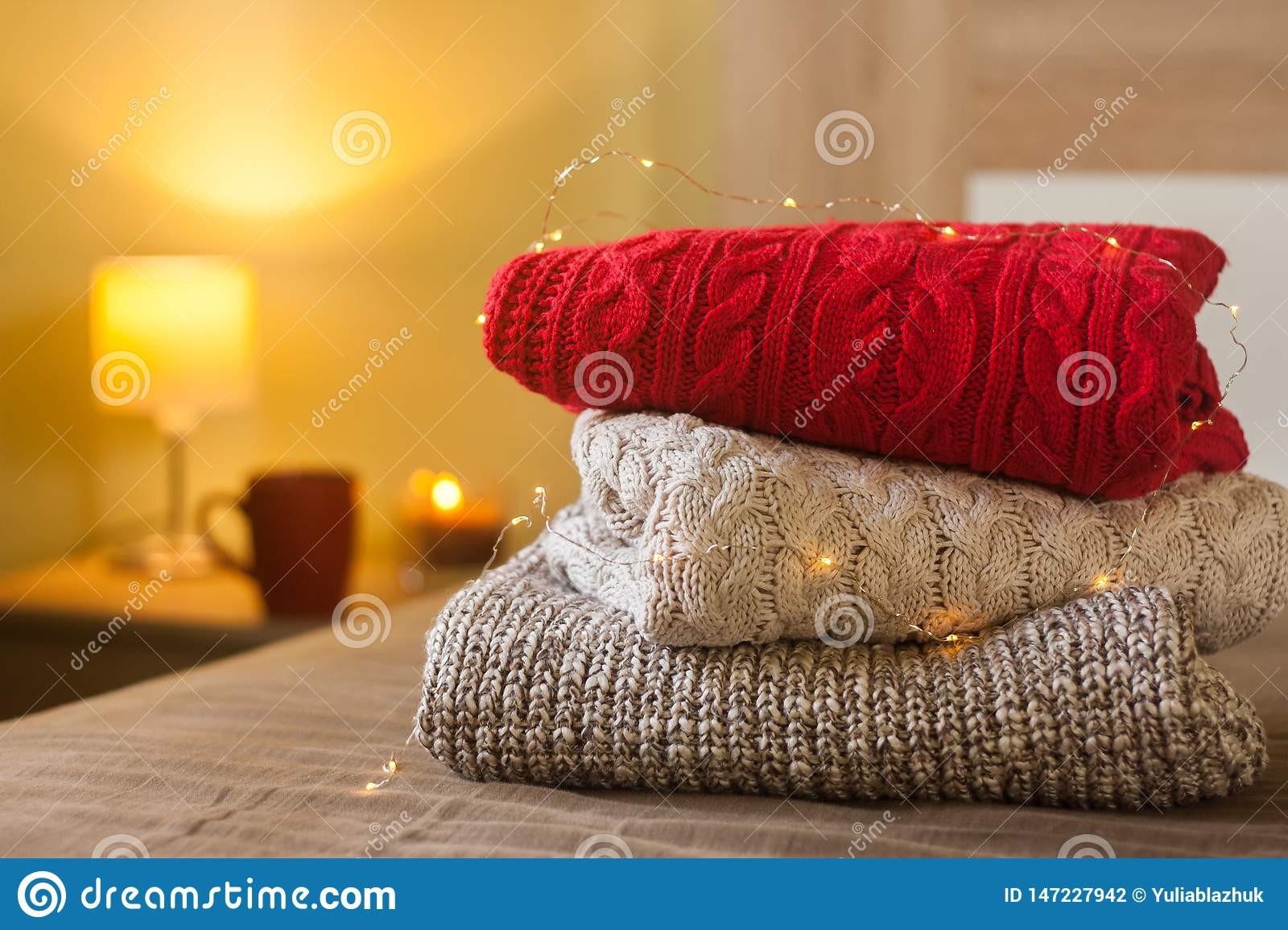 Stack of warm knitted sweaters on a bed decorated with lights and lamp, cup and candle in the background