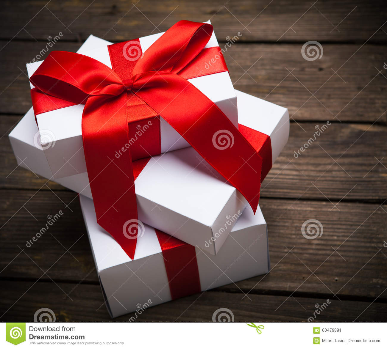 Stack of white Christmas presents on dark wood background