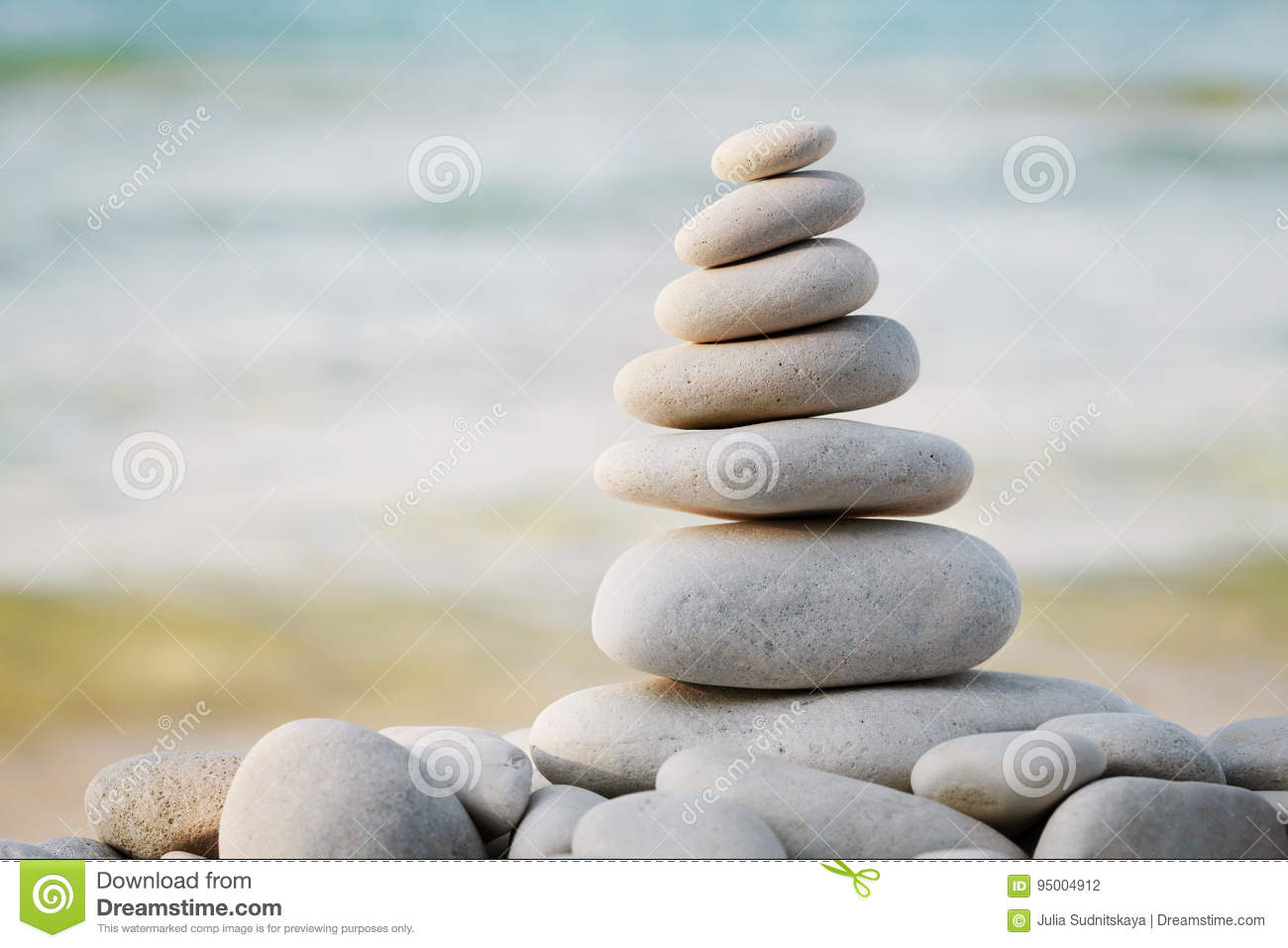 Stack of white pebbles stone against sea background for spa, balance, meditation and zen theme.