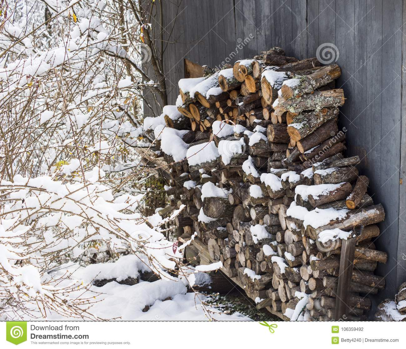 Snow Covers A Stack Of Wood Which Is Stacked Against A Building